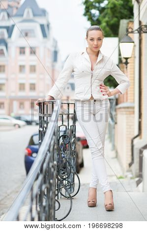 Smiling young lady in white pants and jacket posing outdoors