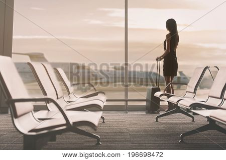 Sunset. Calm graceful business woman is standing back to camera in airport and looking at aircraft through window. She is holding her suitcase thoughtfully. Copy space in left side
