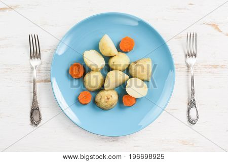 Boiled potatoes and carrots served on flat turquoise plate and vintage forks on white table top view
