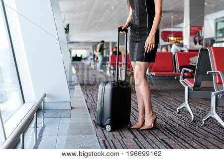 Perfect journey. Graceful elegant lady is standing with luggage near window at modern airport. Close up. Copy space in left side