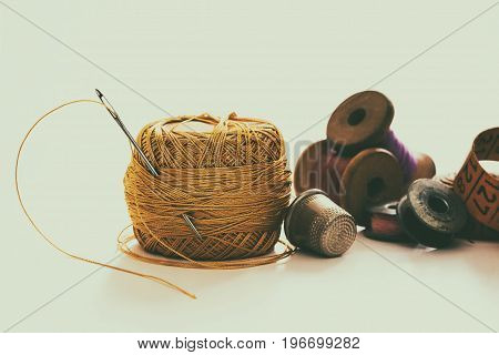 Creative image of sewing accessories for needlework and sewing hobby on white background retro style