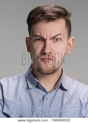 Close up of face of angry man on gray background