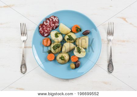 Boiled potatoes carrots and salami served on flat turquoise plate and vintage forks on white table top view