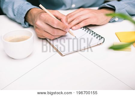 Cropped View Of Male Hands With Coffee Cup Writing In Diary