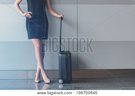 Chic and elegance. Charming young woman is posing at international airport while standing with her suitcase. Copy space in the right side