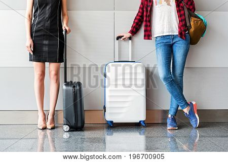Official and casual. Two young ladies are leaning on wall while holding suitcases at international airport. One woman is wearing formal dress other one in jeans. Close up