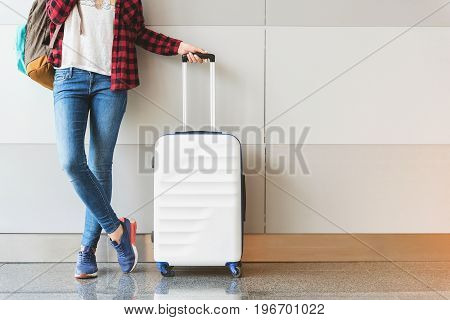Ready to travel. Energetic girl is leaning on wall while holding backpack and suitcase in air terminal. Copy space in the right side