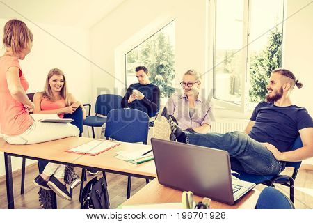 Highschool students having fun during a break in classroom interior