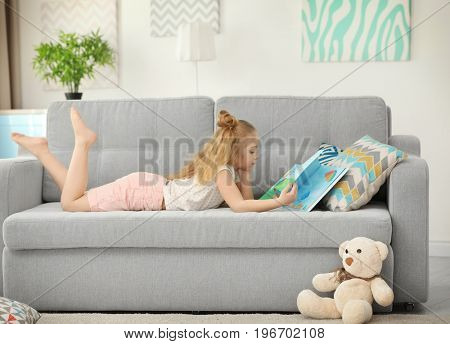 Small girl lying on sofa and reading book in light modern room