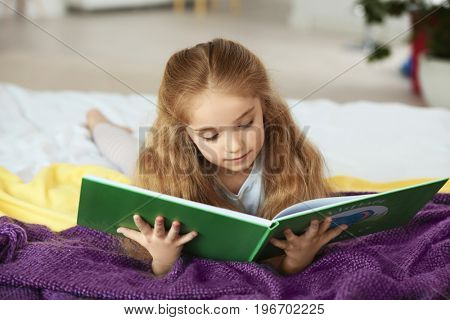 Small girl lying on bed and reading book in light room