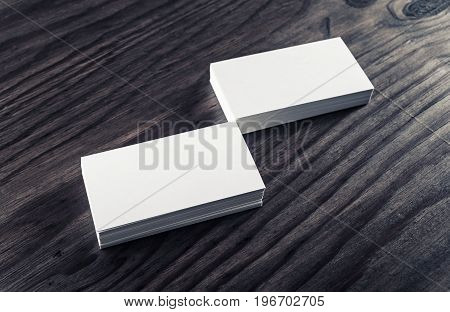 Stacks of blank business cards on vintage wood background. Template for ID. Blank objects for placing your design.