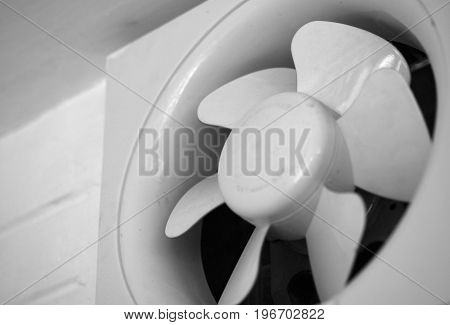 BLACK AND WHITE PHOTO OF EXHAUST FAN MOUNTED ON WALL