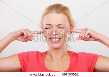 Unhappy blonde woman closing her ears with fingers. Too loud environment face expression concept.