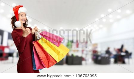 Young woman in Santa hat with shopping bags at store. Boxing Day concept