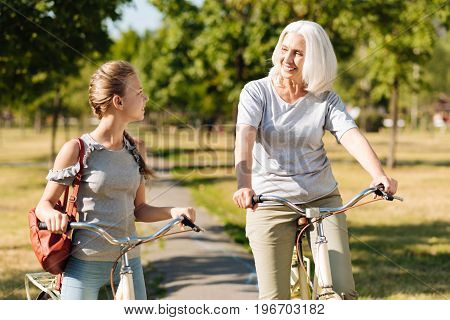 Happy time. Positive smiling woman riding bicycle with her pretty granddaughter and resting in the park together while leading healthy way of life