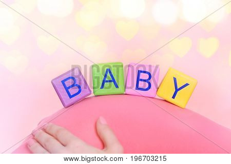 Color cubes with word BABY on abdomen of pregnant woman against Christmas lights background