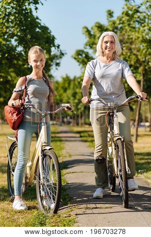 Try out new activity. Positive granddaughter and her grandmother standing in the park and riding bicycles while enjoying weekend
