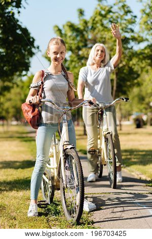 Happy family. Joyful delighted smiling teenager girl riding a bicycle while her gandmother waving her hand in the background