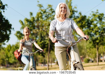 Active lifestyle. Joyful contented senior woman riding a bicycle and resting in the park while her granddaughter following her