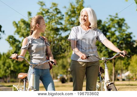 Pleasant time together. Joyful little girl and her positive grandmother talking and standing in the park while resting after riding a bicycle
