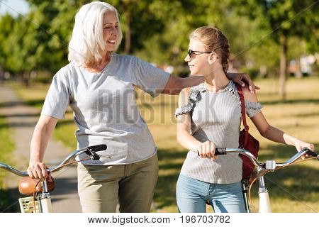 We are friends. Overjoyed smiling aged woman bonding to her granddaughter and standing in the park while riding bicycles