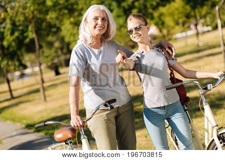 Look here. Positive teenager girl holdign her bicycle and pointing aside while resting in the park with her grandmother