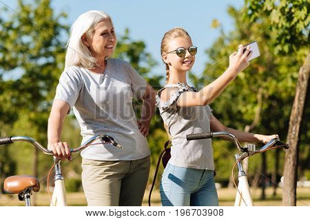 Enjoy sunny days. Positive delighted little girl making selfies and standing in the park with her grandmother after ridign bicycles