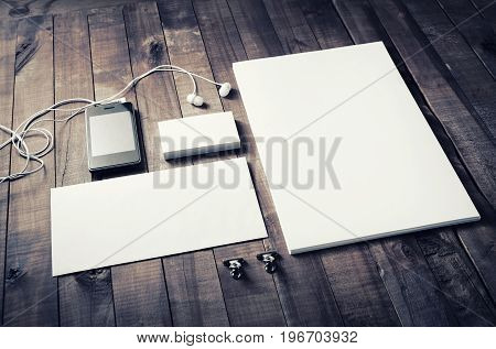 Blank stationery set on vintage wood table background. Template for branding identity. Letterhead business cards envelope smartphone and headphones.