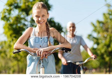 Stay sporty. Cheerful contented girl standing near her bicycle while her grandmother riding in the background
