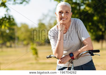 More activities. Joyful beautiful seniuor woman holding handlebar of her bicycle and standing in the park while spending her weekend with pleasure