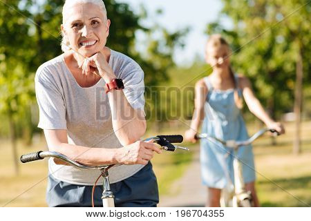 Active way of life. Positive delighted aged woman leaning on the handlebar and resting after riding a bicycle while her granddaughter standing in the background