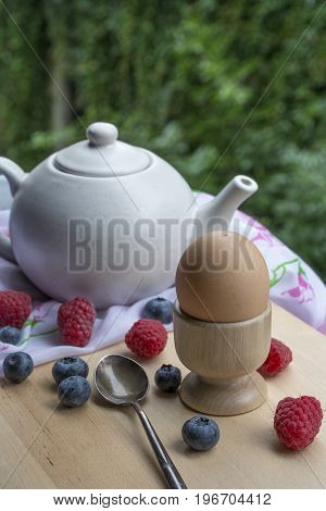 Breakfast with teapot, egg and berries on the wooden table with green leaves as background