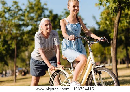 Lets try. Positive smiling teenager girl learning to ride a bicycle and resting in the park while her grandmother pushing her