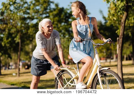 Well done. Joyful smiling senior woman pushing a bicycle and learning her pretty granddaughter riding it