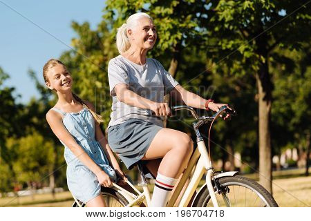 Enjoy the ride. Overjoyed smilign senior woman riding her granddaughter on the bicycle while enjoying weekend in the park together