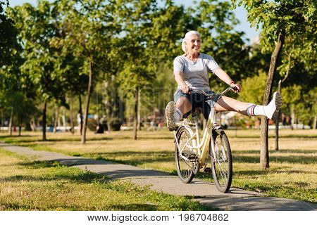 Remember childhood. Cheerful senior woman riding a bicycle and holding her legs apart while enjoyign her weekend