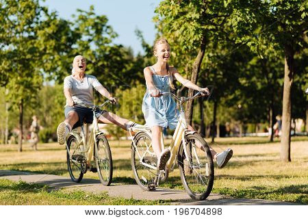 Happy time together. Overjoyed smiling teenager girl and her granddaughter riding bicycles and resting together while expressing their emotions