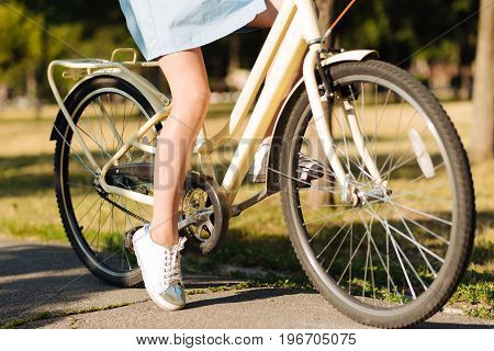 Have a nice ride. Pleasant young girl sitting on the bicycle and resting in the park while enjoying sunny weather