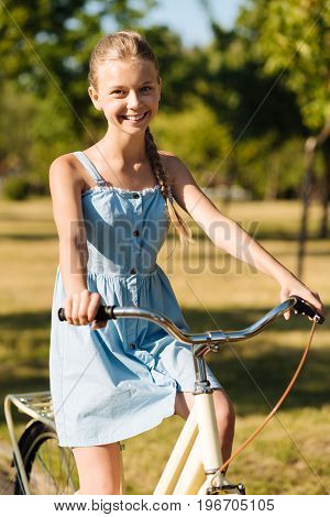 Sporty activity. Cheerful smiling pretty girl riding her bicycle and resting in the park while enjoying her weekend