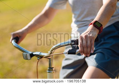 Live life fully. Pleasant adult woman holding a handlebar and riding a bicycle while enjoying time outdoors