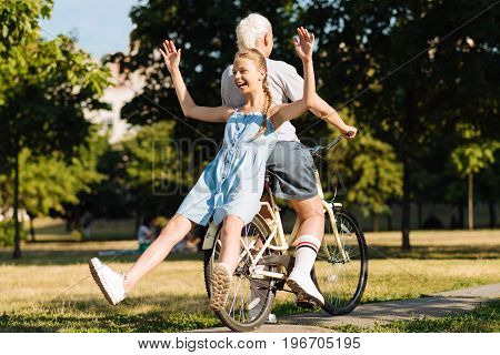 Have some fun. Cheerful delighted little girl sitting on the bicycle while grandmother riding it and spending leisure time together