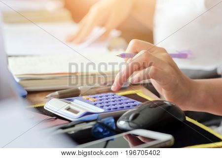close up female hands of accountant with calculator and pen. business accounting background.
