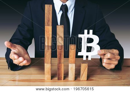 Business Economic crisis concept Businessman holding showing bitcoin symbol concede decrease of price and Depression of the economy. wooden block of the financial crisis of income in bitcoins.