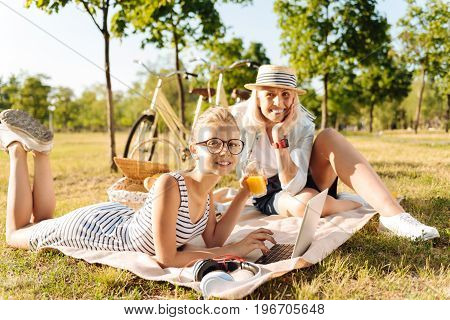 Pleasant summer day. Cheerful delighted young girl using laptop and drinking juice while resting in the park with her grandmother