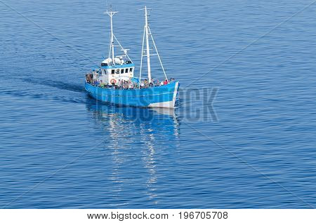 Copenhagen, Denmark-July 14, 2017: Party fishing boat with fishermen, checking out the cruise ship