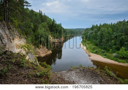 View from cliff on sandstone outcrops river and forest. Erglu Cliffs on the bank of the Gauja river.