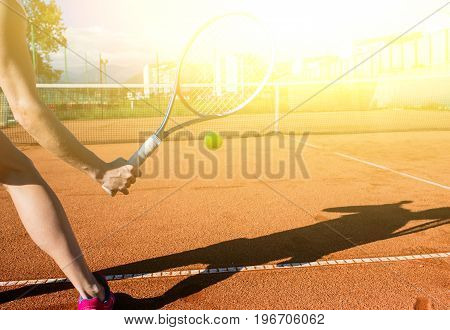 Closeup photo of female hand with tennis racket hitting the ball