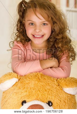 A portrait of a young pretty girl smiling and posing over her teddy bear head in a doctor office background.