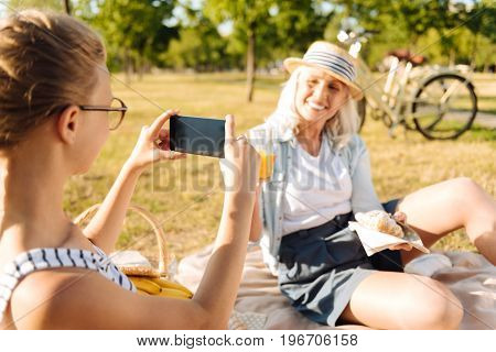 Stay positive. Cheerful pleasant teenager girl holding her phone and taking photos of her grandmother while enjoying time in the park on a picnic