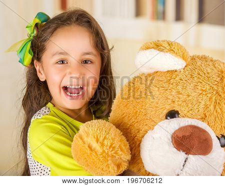 A portrait of a young pretty girl smiling and hugging her teddy bear over blurred background.